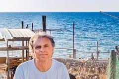 Adulto de tres días de la barba en la orilla de mar Foto de archivo libre de regalías