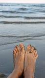 Adulto descalzo en la orilla de la playa mientras que él descansa y real Imagenes de archivo