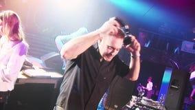 Adulto DJ que gira na plataforma giratória no clube noturno Go vai meninas na fase iluminação Sorriso na câmera video estoque