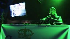 Adulto DJ in vetri che filano alla piattaforma girevole sul partito in night-club intrattenimento Riflettore verde video d archivio
