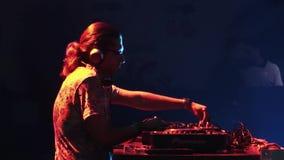 Adulto DJ in vetri che filano alla piattaforma girevole sul partito in night-club intrattenimento Riflettori variopinti archivi video
