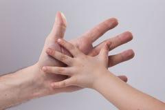 adulto e child& x27; ternura tocante da ajuda da mão de s Imagem de Stock Royalty Free
