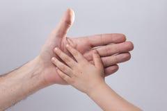 adulto e child& x27; ternura tocante da ajuda da mão de s Fotografia de Stock