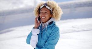Adulto feliz en mono de nieve con el teléfono celular almacen de video