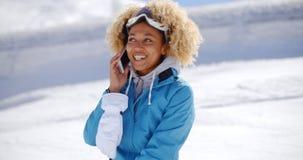 Adulto feliz en mono de nieve con el teléfono celular Imagenes de archivo