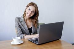 Adulto femenino joven lindo que trabaja en el ordenador portátil en el escritorio al lado de la taza de café Imagenes de archivo