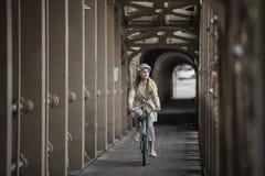 Adulto femenino joven que completa un ciclo sobre un puente Imagen de archivo libre de regalías