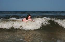 Adulto femenino joven que juega en el océano Foto de archivo