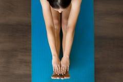 Adulto femminile che allunga su una stuoia di yoga nella classe fotografia stock libera da diritti