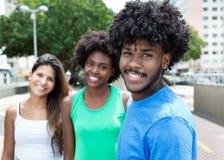 Adulto joven afroamericano con dos muchachas hermosas en la ciudad en el verano Foto de archivo libre de regalías