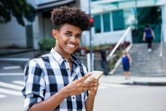 Adulto joven afroamericano usando el teléfono móvil para Internet Fotos de archivo libres de regalías