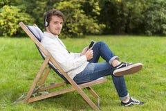 Adulto joven barbudo que escucha la música que se sienta en parque verde Imagen de archivo libre de regalías