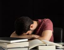 Adulto joven cansado que duerme sobre los libros Imagen de archivo libre de regalías