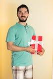 Adulto joven con la caja de regalo roja para la Navidad Imagenes de archivo