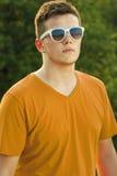 adulto joven con la relajación de las gafas de sol al aire libre Imagenes de archivo