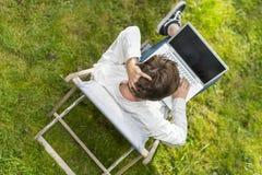 Adulto joven con un problema o pensamiento con el ordenador portátil Fotografía de archivo libre de regalías