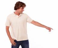 Adulto joven encantador que señala a su izquierda Fotografía de archivo