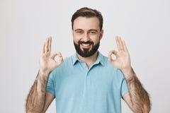 Adulto joven hermoso con la barba y sonrisa brillante, mostrando gesto o el approvement aceptable con dos manos, sobre gris Fotos de archivo libres de regalías