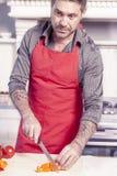 Adulto joven hermoso en cocina moderna mientras que prepara la verdura Imagen de archivo libre de regalías