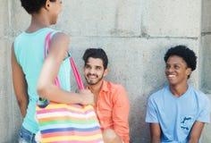 Adulto joven latino y afroamericano que habla con la muchacha Foto de archivo libre de regalías