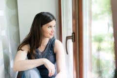 Adulto joven mirando la ventana Imagenes de archivo