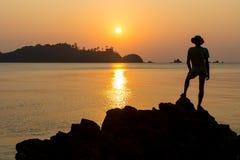 Adulto joven que aumenta los brazos al mar en las manos de la puesta del sol para arriba Fotografía de archivo libre de regalías
