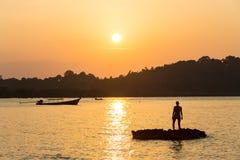 Adulto joven que aumenta los brazos al mar en las manos de la puesta del sol para arriba Foto de archivo