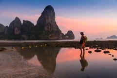 Adulto joven que aumenta los brazos al mar en las manos de la puesta del sol para arriba Fotografía de archivo