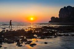 Adulto joven que aumenta los brazos al mar en las manos de la puesta del sol para arriba Foto de archivo libre de regalías