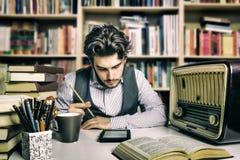 Adulto joven que lee un ebook Fotografía de archivo libre de regalías