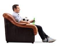 Adulto joven que sostiene un fútbol y una cerveza Imágenes de archivo libres de regalías