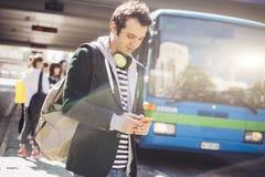 Adulto joven usando al aire libre móvil en la ciudad Imagen de archivo libre de regalías