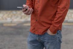 Adulto joven usando el teléfono móvil Foto de archivo libre de regalías