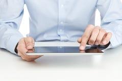 Adulto joven usando la tablilla digital Imagenes de archivo