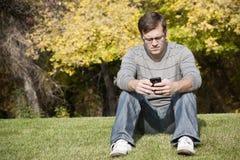 Adulto joven usando su teléfono elegante Imágenes de archivo libres de regalías