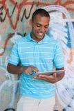 Adulto joven usando una PDA de la PC de la tableta Foto de archivo