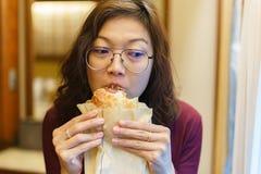 Adulto maduro de la mujer asiática que come los carbohidratos del pan Foto de archivo