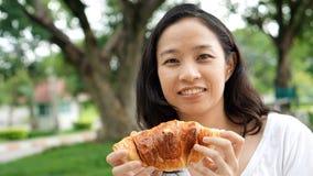 Adulto maduro de la mujer asiática que come los carbohidratos del pan Imágenes de archivo libres de regalías
