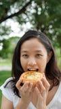 Adulto maduro de la mujer asiática que come los carbohidratos del pan Imagen de archivo libre de regalías