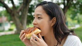 Adulto maduro de la mujer asiática que come los carbohidratos del pan Fotos de archivo