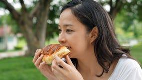 Adulto maduro de la mujer asiática que come los carbohidratos del pan Imagenes de archivo