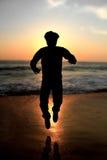 Adulto maschio della siluetta che salta ad una spiaggia immagini stock