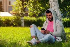 Adulto masculino feliz usando su smartphone en parque Imagen de archivo libre de regalías