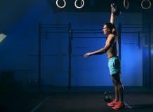 Adulto masculino joven que ejercita con el kettlebell en gimnasio Fotos de archivo libres de regalías