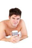Adulto masculino joven que sostiene una taza de té en su cama Foto de archivo libre de regalías