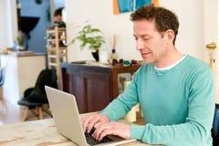 Adulto masculino maduro que se sienta en la tabla en casa usando el ordenador portátil Imagen de archivo