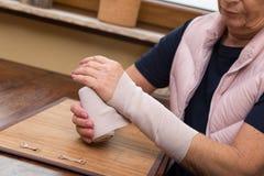 Adulto mayor con el vendaje del brazo Imagen de archivo libre de regalías
