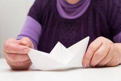 Adulto mayor con un barco de papel Imagenes de archivo