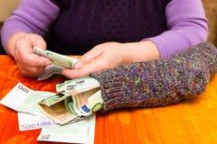 Adulto mayor con un calcetín lleno de dinero Imagen de archivo libre de regalías