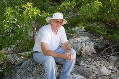 Adulto mayor en roca Fotos de archivo libres de regalías